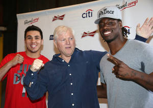 "Photo - Michael King, center, president of King Sports, poses with heavyweight boxers Charles Martin, left, and Alex Flores during a weigh-in Tuesday, April 15, 2014, in Santa Monica, Calif., for Wednesday's ""Boxing at Baker"" at the Baker Hangar in Santa Monica, Calif. King is determined to return boxing to its former glory, and the wealthy television executive has spent millions in his pursuit over the last few years. His latest venture is a series of shows in Santa Monica, where he expects Hollywood talent will watch his up-and-coming fighters' growth into stars. (AP Photo/Nick Ut)"