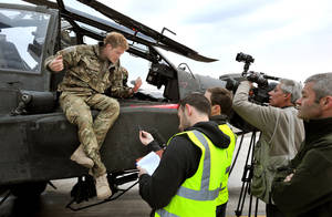 photo - FILE - In this Dec. 12, 2012 file photo, Britain's Prince Harry talks to a TV crew after making his early morning pre-flight checks on the flight line, at Camp Bastion southern Afghanistan. During Prince Harry's 20-week deployment in Afghanistan, he served as an Apache helicopter pilot with the Army Air Corps. (AP Photo/John Stillwell, Pool, File)