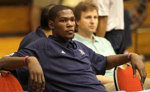 photo - Oklahoma City Thunder's Kevin Durant watches the team warm up prior to an NBA  summer  league basketball game against the Philadelphia 76ers in Orlando, Fla., Wednesday, July 7, 2010. Durant agreed to a five-year contract extension with the team Wednesday, according to an update on his Twitter page. (AP Photo/John Raoux)