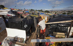 Photo -   A man prepares his shack in a area occupied by Members of the Brazil's Landless Movement (MST) in Embu das Artes, outskirt of Sao Paulo, Brazil, Monday, May 7, 2012. According to the Landless Movement, there are about 8,000 people living in over 3,000 tents in Embu, an area with three natural springs and 4.7 million square feet of native forest that has grown into the country's largest landless occupation.Conflicts over land in Brazil increased last year, and there are at least two that could turn into violent conflagrations at any moment, although the number of rural activists killed nationally went down slightly, according to a report released Monday by a watchdog group that has long kept a tally of threats and murders. (AP Photo/Andre Penner)