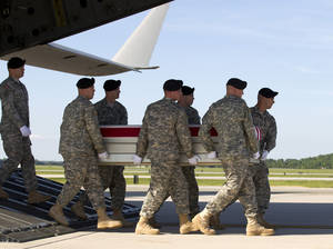 Photo - FILE - In this June 1, 2014, file photo, an Army carry team, carries the transfer case containing the remains of Army Pfc. Jacob H. Wykstra of  Thornton, Colo., upon arrival at Dover Air Force Base, Del. The Department of Defense announced the death of Wykstra who was supporting Operation Enduring Freedom in Afghanistan. he deteriorating situation in Iraq is giving Congress pause about President Barack Obama's plan to withdraw U.S. forces from Afghanistan by the end of 2016. Lawmakers fear that the hard-fought gains in Afghanistan could be wiped out by a resurgent Taliban. Senior Obama administration officials insist that Afghanistan is not Iraq.  ( AP Photo/Jose Luis Magana, File)