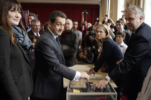Photo -   French President and UMP candidate Nicolas Sarkozy, center left, casts his vote for the second round of the presidential elections as his wife Carla Bruni-Sarkozy, left, looks on in Paris Sunday May 6, 2012. The election could see Socialist challenger Francois Hollande defeat incumbent Sarkozy by capitalizing on public anger over the government's austerity policies. (AP Photo/Michel Euler, Pool)