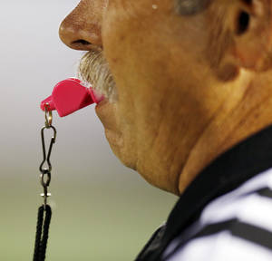 Photo - An official uses a pink whistle as part of Win-Win Week to raise cancer awareness during a high school football game between Edmond Memorial and Deer Creek at Wantland Stadium in Edmond, Okla., Thursday, Sept. 13, 2012. Photo by Nate Billings, The Oklahoman