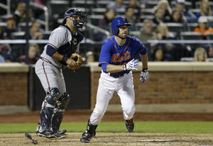 Photo - Atlanta Braves catcher Gerald Laird, left, joins New York Mets' Ike Davis as they watch Davis's eighth-inning, two-run, single in the Mets 4-2 victory during a baseball game at Citi Field in New York, Sunday, May 26, 2013. (AP Photo/Kathy Willens)