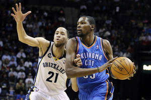 Photo - Oklahoma City Thunder's Kevin Durant, right, is guarded by Memphis Grizzlies' Tayshaun Prince (21) during the first half of an NBA basketball game in Memphis, Tenn., Wednesday, March 20, 2013. (AP Photo/Danny Johnston) ORG XMIT: TNDJ102