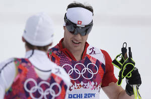 Photo - Switzerland's Dario Cologna smiles as he wins the gold during the men's 15K classical-style cross-country race at the 2014 Winter Olympics, Friday, Feb. 14, 2014, in Krasnaya Polyana, Russia. (AP Photo/Matthias Schrader)