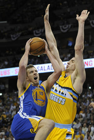 Photo - Golden State Warriors forward David Lee, left, drives the lane against Denver Nuggets center Kosta Koufos, right, in the first quarter of Game 1 in the first round of the NBA basketball playoffs on Saturday, April 20, 2013, in Denver. (AP Photo/Chris Schneider) ORG XMIT: COCS101