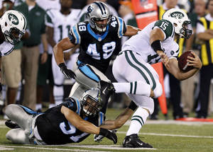 Photo -   New York Jets quarterback Tim Tebow (15) avoids tackles from Carolina Panthers' Jordan Senn (57) and J.J. Finley (49) during the second half of a preseason NFL football game Sunday, Aug. 26, 2012, in East Rutherford, N.J. (AP Photo/Julio Cortez)
