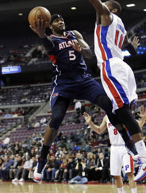 photo - Atlanta Hawks forward Josh Smith (5) shoots around Detroit Pistons center Greg Monroe (10) during the first quarter of an NBA basketball game at the Palace in Auburn Hills, Mich., Monday, Feb. 25, 2013. (AP Photo/Carlos Osorio)