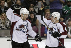 Photo - Colorado Avalanche center Paul Stastny, left, and Tyson Barrie (4) celebrate a power play goal by Stastny against the Dallas Stars in the second period of an NHL hockey game, Monday, Jan. 27, 2014, in Dallas. (AP Photo/Tony Gutierrez)