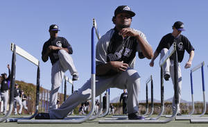 Photo - Colorado Rockies pitcher Manuel Corpas, center, ducks under a hurdle in front of teammates LaTroy Hawkins, left, and Greg Burke, right, during spring training baseball practice, Monday, Feb. 17, 2014, in Scottsdale, Ariz.  (AP Photo/Gregory Bull)