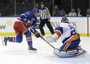 photo - New York Rangers&#039; J.T. Miller, left, scores a goal past New York Islanders goalie Evgeni Nabokov, right, during the second period of the NHL hockey game in New York, Thursday, Feb. 7, 2013.  (AP Photo/Seth Wenig)