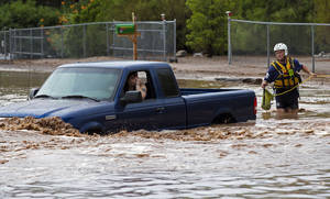 Photo - A man an woman sit in a truck on Tomahawk Rd. flooded by rain waters in Apache Junction, Ariz., Sunday, July 21, 2013. Mesa Fire Dept. were able to walk the two out safely. (AP Photo/The Arizona Republic, Michael Chow)