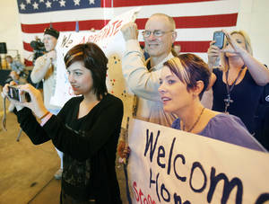 Photo - Halsey Musselman (left), Bill Pearsall, and Ashley Musselman watch and cheer as Oklahoma National Guard soldiers return from Afghanistan to a welcome home ceremony in Oklahoma City, OK, Tuesday, March 13, 2012,  By Paul Hellstern, The Oklahoman
