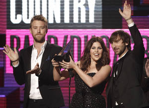 Photo -   FILE - In this Nov. 20, 2011, file photo Lady Antebellum musical group members from left, Charles Kelley, Hillary Scott and Dave Haywood, accept the award for country band, duo or group at the 39th Annual American Music Awards on in Los Angeles. Students from the wrecked school awaited word Tuesday, March 20, 2012, about whether on online campaign supported by other schools in their state and beyond will land them a prom-night performance by Grammy-winning country trio Lady Antebellum. (AP Photo/Matt Sayles, File)