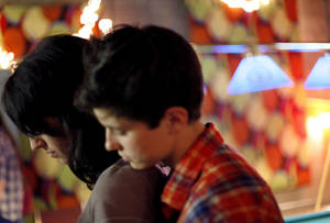 Photo - Katie Hill, left, and her boyfriend look at a text as they attend a party for Katie at Openarms Youth Project in Tulsa. Katie recently graduated from high school, turned 18 and went to California to have surgery.