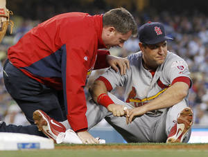 photo -   A trainer checks the right knee of St. Louis Cardinals first baseman Lance Berkman, right, who sustained an injury while forcing out Los Angeles Dodgers' Justin Sellers at first base to end the second inning of a baseball game on Saturday, May 19, 2012, in Los Angeles. (AP Photo/Danny Moloshok)
