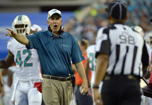 Photo - Miami Dolphins head coach Joe Philbin has words with head linesman Greg Bradley (98) during the first half of an NFL preseason football game against the Jacksonville Jaguars, Friday, Aug. 9, 2013, in Jacksonville, Fla. (AP Photo/Phelan M. Ebenhack)
