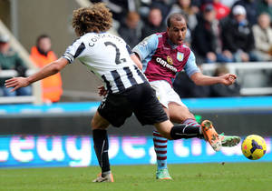 Photo - Aston Villa's Gabriel Agbonlahor, right, has a shot towards goal past Newcastle United's captain Fabricio Coloccini, left, during their English Premier League soccer match at St James' Park, Newcastle, England, Sunday, Feb. 23, 2014. (AP Photo/Scott Heppell)
