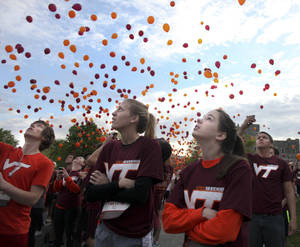 Photo -   FILE - In this Saturday, April 14, 2012 file photo, Paige Eckerd, right, and Kristy McCain, center, look skyward at released balloons at the start of a Run in Remembrance on the Virginia Tech campus in Blacksburg, Va. The 3.2-mile Run in Remembrance for the victims of the April 16, 2007, Virginia Tech shootings had about 6,500 participants registered in advance for the event in honor of the 32 killed in the deadliest mass shooting in modern U.S. history. Each anniversary since the April 2007, massacre on the Virginia Tech campus, classes have been suspended for the day in memory of the 32 students and faculty killed in the rampage by a lone gunman who then killed himself. On Monday, April 16, 2012, the fifth anniversary of the deadliest mass shooting in modern U.S. history, the 28,000 students on campus will head to class to honor the 32. (AP Photo/The Roanoke Times, Matt Gentry, File)