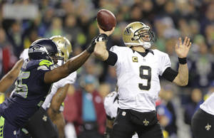 Photo - Seattle Seahawks defensive end Cliff Avril, left, causes New Orleans Saints quarterback Drew Brees (9) to fumble in the first half of an NFL football game, Monday, Dec. 2, 2013, in Seattle. Seahawks defensive end Michael Bennett recovered the fumble and ran for a touchdown. (AP Photo/Scott Eklund)