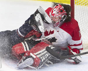 Photo - Canada's goalie Shannon Szabados, right, faces the skates of United States' Meghan Duggan after  Duggan slid into her during pre-Olympic women's hockey game action in Calgary, Alberta, Thursday, Dec. 12, 2013. (AP Photo/The Canadian Press, Larry MacDougal)