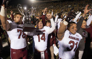 Photo - South Carolina's Connor Shaw, center, holds the Mayors Cup as he celebrates with teammates Cody Gibson, left, and Jordan Diaz, right, after the team defeated Missouri 27-24 in an NCAA college football game Saturday, Oct. 26, 2013, in Columbia, Mo. (AP Photo/L.G. Patterson)