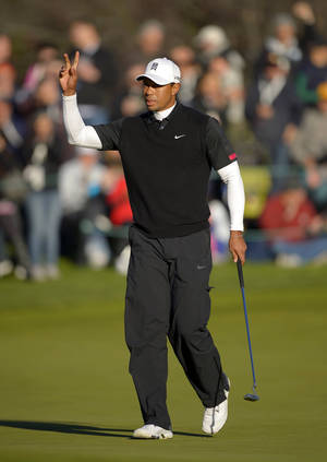 Photo - Tiger Woods acknowledges fans after making a birdie putt on the 18th green during the third round of the Northwestern Mutual World Challenge golf tournament at Sherwood Country Club, Saturday, Dec. 7, 2013, in Thousand Oaks, Calif. (AP Photo/Mark J. Terrill)