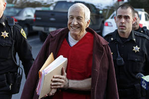 Photo - FILE - In this Jan. 10, 2013 file photo, former Penn State University assistant football coach Jerry Sandusky, center, arrives at the Centre County Courthouse for a post-sentence motion in Bellefonte, Pa. Sandusky lost a bid for a new trial Wednesday, Jan. 30, 2013 when Judge John Cleland rejected his argument that his lawyers were not given enough time to prepare for the three-week proceeding that ended with a 45-count guilty verdict. Sandusky is serving a 30- to 60-year prison sentence after being convicted in June of 45 counts of child sexual abuse. (AP Photo/Gene J. Puskar, File)