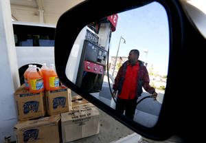 Photo -   FILE-In this Wednesday, Sept. 12, 2012, file photo, gas station attendant Youssouf Soukouna, 42, pumps gas into a vehicle at a LukOil station where all levels of gas were priced at $4.99, in Newark, N.J. Higher gas prices are crimping consumer spending and slowing the already-weak U.S. economy. And they could get worse in the coming months. The Federal Reserve this week took steps to boost economic growth. But those stimulus measures are also pushing oil prices up. If gas prices follow, consumers will have less money to spend elsewhere. (AP Photo/Julio Cortez, File)