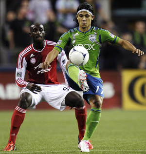 photo -   Seattle Sounders' Fredy Montero, right, kicks the ball in front of Portland Timbers' Mamadou Danso in the first half of an MLS soccer match, Sunday, Oct. 7, 2012, in Seattle. The Sounders won 3-0. (AP Photo/Ted S. Warren)