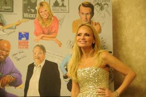 Photo - Actress/singer Kristin Chenoweth poses with the portrait commemorating the 2011 induction class for the Oklahoma Music Hall of Fame on Nov. 10, 2011, in Muskogee. Photo by Adam Kemp, For The Oklahoman. <strong></strong>