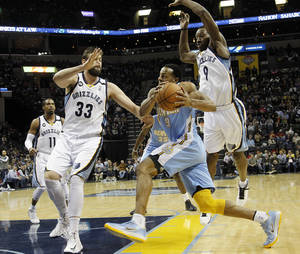 Photo - Denver Nuggets guard Andre Iguodala, center, drives to the basket against Memphis Grizzlies defenders Marc Gasol (33), of Spain, and Tony Allen, right, in the first half of an NBA basketball game on Saturday, Dec. 29, 2012, in Memphis, Tenn. (AP Photo/Lance Murphey)