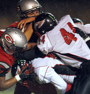 Photo - Del City's defense hits U.S. Grant quarterback Carlos Morales during a 2011 game at C.B. Speegle Stadium. The Eagles have dropped down to Class 5A this season after going 1-9 in 2011. Photo from The Oklahoman Archives