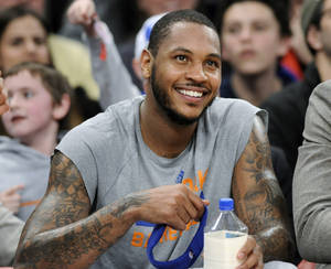 Photo - FILE - In this Jan. 24, 2014 file photo, New York Knicks' Carmelo Anthony smiles as he watches from the bench during the fourth quarter of an NBA basketball game against the Charlotte Bobcats,  at Madison Square Garden in New York. Signing day has arrived in the NBA, if the biggest free agents care to grab their pens. But it's unclear if Anthony, Chris Bosh and Dwyane Wade _ who all might be waiting on LeBron James to go first _ are ready. (AP Photo/Bill Kostroun, File)