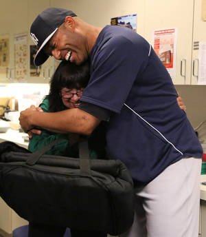 Photo - In this photo provided by the Oakland Athletics, New York Yankees' Mariano Rivera embraces A's mail room employee Julie Vasconcellos prior to the baseball game between the A's and Yankees Wednesday, June 12, 2013, in Oakland, Calif. (AP Photo/Oakland Athletics)