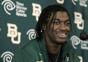 Photo -   FILE - In this Jan. 11, 2012, file photo, Heisman Trophy winner Robert Griffin III attends a news conference after announcing that he would skip his senior year at Baylor and enter the NFL draft in Waco, Texas. FOXSports.com is reporting the Washington Redskins have a deal in place to acquire the No. 2 pick in the NFL draft and plan to take Griffin. (AP Photo/Tony Gutierrez, File)