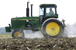 Photo - FILE - In this April 2, 2012 file photo, Derek Long uses a John Deere tractor to disk and cultivate a field in preparation for planting corn in Loami, Ill.  Deere & Co. reports quarterly earnings on Wednesday, Feb. 12, 2014. (AP Photo/Seth Perlman, File)