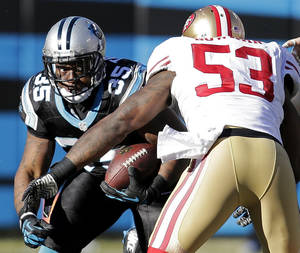 Photo - Carolina Panthers fullback Mike Tolbert (35) runs into San Francisco 49ers inside linebacker NaVorro Bowman (53) during the second half of a divisional playoff NFL football game, Sunday, Jan. 12, 2014, in Charlotte, N.C. (AP Photo/Chuck Burton)