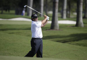 Photo - Patrick Reed hits from the eighth fairway during a continuation of the first round of the Cadillac Championship golf tournament, Friday, March 7, 2014, in Doral, Fla. Play was suspended before the end of play Thursday due to severe weather. (AP Photo/Lynne Sladky)