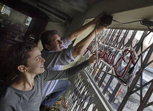 photo - In this  Tuesday, Dec. 4, 2012, photo, General Manager Ludmila Silva and proprietor Adam Weprin, of the Bridge Cafe, in New York's South Street Seaport, take down the restaurant's neon sign at the restaurant. Like many small business owners in the Northeast whose stores, restaurants, factories and offices were devastated or destroyed by the Oct. 29 storm, Weprin is hoping that federal, state and local officials will quickly come up with grants to help him rebuild and survive. (AP Photo/Richard Drew)