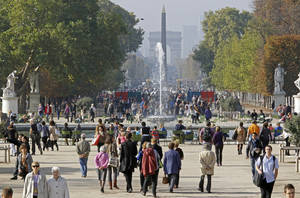 photo -   This Oct. 23, 2012 photo shows people strolling in the Tuileries gardens, with the Arc de Triomphe in background, in Paris. The 400-year-old Tuileries gardens sitting tranquilly in the heart of the capital between the Louvre Museum and the Place de la Concorde offers a place to relax with their ornate fountains, magical statues and fresh air. (AP Photo/Remy de la Mauviniere)