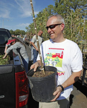 Photo - Above: Jim Friedemann, of Norman, picks up  a free tree at a city- sponsored tree giveaway last year. Norman  residents can now  register for more free trees, beginning Tuesday.