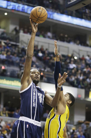 Photo - Oklahoma City Thunder's Kevin Durant, left, shoots over Indiana Pacers' Paul George during the first half of an NBA basketball game on Friday, April 5, 2013, in Indianapolis. (AP Photo/Darron Cummings)  ORG XMIT: NAF104