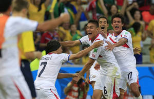 Photo - Costa Rica's Oscar Duarte, center, celebrates after scoring his side's second goal during the group D World Cup soccer match between Uruguay and Costa Rica at the Arena Castelao in Fortaleza, Brazil, Saturday, June 14, 2014.   (AP Photo/Bernat Armangue)