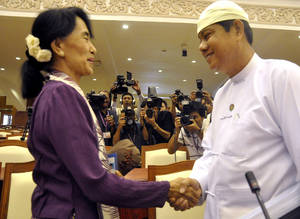 Photo -   Myanmar opposition leader Aung San Suu Kyi, left, shakes hands with Htay Oo, right, general secretary of Union Solidarity and Development party headed by President Thein Sein, as she attends a regular session of Myanmar Lower House in Naypyitaw, Myanmar, Wednesday, May 2, 2012. Suu Kyi was sworn in to Myanmar's military-backed parliament Wednesday, taking public office for the first time since launching her struggle against authoritarian rule nearly a quarter century ago. (AP Photo/Khin Maung Win)