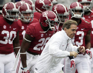 Photo - Alabama head coach Nick Saban leads his team onto the field for an NCAA college football game against Chattanooga in Tuscaloosa, Ala., Saturday, Nov. 23, 2013. (AP Photo/Dave Martin)