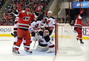 photo - Carolina Hurricanes' Jussi Jokinen, left, of Finland, celebrates a goal by teammate Jeff Skinner, right, against New Jersey Devils' goalie Johan Hedberg (1), of Sweden, and defender Marek Zidlicky (2), of the Czech Republic, during the second period of an NHL hockey game in Raleigh, N.C., Saturday, March 9, 2013. (AP Photo/Ted Richardson)