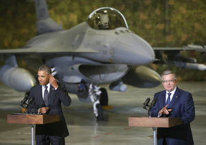 Photo - U.S. President Barack Obama and Poland's President Bronislaw Komorowski make statements and meet with U.S. and Polish troops at an event featuring four F-16 fighter jets, two American and two Polish, as part of multinational military exercises, in Warsaw, Poland, Tuesday, June 3, 2014. (AP Photo/Charles Dharapak)