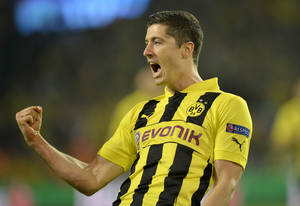 Photo - FILE - In this April 24, 2013 file picture Dortmund's Robert Lewandowski of Poland celebrates scoring the opening goal during the Champions League semifinal first leg soccer match between Borussia Dortmund and Real Madrid in Dortmund, Germany. Bayern Munich signed Robert Lewandowski from Bundesliga rival Borussia Dortmund on a free transfer on Saturday Jan. 4, 2014, with the deal taking effect at the end of the season. Bayern announced in a statement that Lewandowski, who pushed for a move to the Bavarian powerhouse last summer, signed a five-year deal through June 2019 that will take effect from July 1.   (AP Photo/Martin Meissner,File)